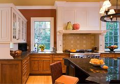 Don't always do the expected. Here instead of a frame inside the area over the stove, a pattern visually expands the space. Ceiling color and matching tile.