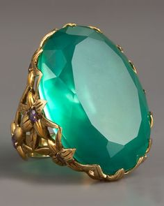 Stephen Dweck     Large Agate & Delphinium Ring Oval-cut green Agate Stone. Bronze setting forms delphinium motif. Round-cut Amethyst adorns Floral centers. Made in USA. 395.00 USD