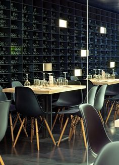 No lack of wine in this restaurant with its black Eames Plastic Side Chairs.