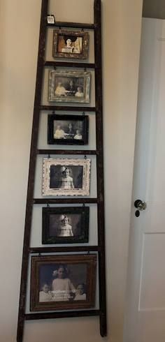 old ladder and old pictures hanging from each rung in old picture frames....