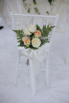 La sedia degli sposi con bouquet di rose salmone e bianche e felce (simbolo di sincerità) legate con un nastro di raso bianco.
