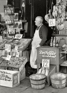 """November 1939. Waco, Texas. """"Proprietor of small store in market square."""" Pop bottles on the cooler: Woosies, Double Line and Double Cola. 35mm nitrate negative by Russell Lee for the Farm Security Administration."""