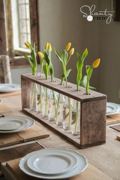 Place recycled glass soda bottles in a pine or whitewood frame and fill with fresh Mother's Day flowers for a breathtaking centerpiece she'll love. Get the tutorial at Shanty 2 Chic.   - CountryLiving.com