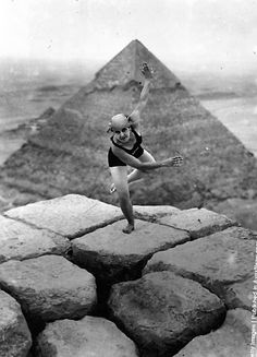 A woman is dancing on the Sphinx. Behind her are the Pyramids of Giza 1928