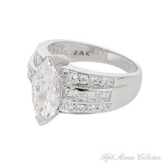 """There's something affectionately timeless about this dazzling sterling silver ring… maybe it's the unique depth and everlasting brilliance of the center marquis cut AAA cubic zirconia. Or the ageless setting… a wide band featuring two rows of clear rounds and a center row of baguettes, designed to accent the center stone in every light. Finished in your choice of rich rhodium or gleaming gold, this ring is a true """"Timeless Beauty""""."""