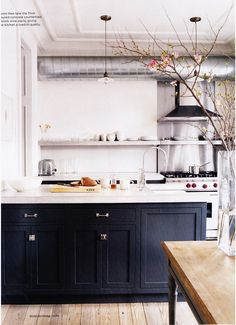 I like to see contrast in kitchens and block colours - the traditional cupboards, wooden table and dried flowers help make this kitchen homely and contrast well with the silver appliances