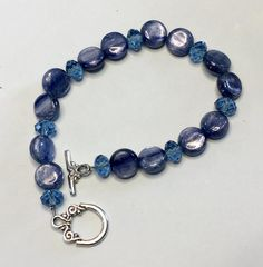 Blue flat rounds and fasceted beads enhanced with antiqued pewter toggle clasp. Bracelet measures just about and nicely fits a to inch wrist. Blue Flats, Wire Wrapped Necklace, Antique Pewter, Wedding Themes, Blue Wedding, Beaded Bracelets, Beads, Antiques, Earrings