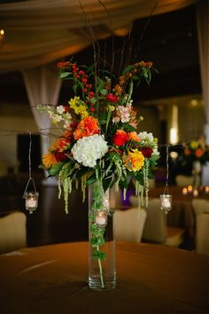 The second table arrangement was an airy mound of the wedding flowers atop a glass cylinder with a submerged stem of belles of Ireland. Hanging votive candles were attached to branches and brought ambiance to each table.   by Dorothy McDaniel's Flower Market; Spindle Photography