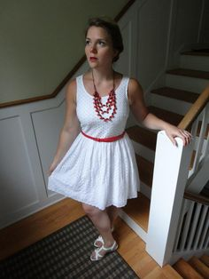 white sandals, white eyelet sleeveless dress, red belt, red statement necklace, red lips