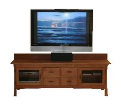 Contemporary Craftsman 4-Drawer Media Console featuring glass doors shown in natural cherry. Customize in your choice of solid cherry, maple, or walnut woods.  This media console is topped with an eco-friendly, non-toxic oil finish to protect and enhance the natural beauty of the wood!