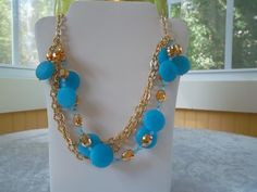 Blue frosted beads with amber and opaque blue crystals on gold tone chain.