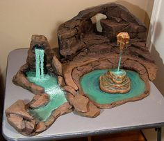 How to make rock caves and waterfalls using pink Styrofoam and hot glue! - Tanu's note: black rocks, neon green water and skeletons sitting on rocks