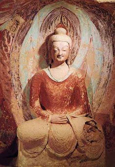 """Dunhuang - A superb example of a smiling (""""Early Greek"""") Central Asian Buddha. At his broken knee one can see the straw and wood with which Central Asian clay statues are filled. Buddha Maitreya, Cave 259, Northern Wei, around 470 AD."""