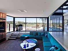 Janelas que cobrem as paredes por completo emolduram os ambientes desta casa australiana. Assim, espaços como a sala de estar são valorizados por luz natural abundante e a vista da área externa. Um recorte no piso da sala define o home theater, abrigando um sofá seccional verde azulado aconchegante. (📷Ben Hosking | via @homedsgn) #sala #living #hometheater #australia #inspo #inspiration #inspiração #inspiracao #casa #home #house #apartment #apartamento #decor #decoration #decoração…