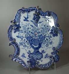 Dutch Delft blue and white plaque, 18th century, of rococo form decorated with a vase of flowers and two birds, height: 13in. 33cm.