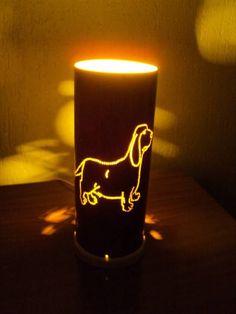 Linda luminária do cãozinho da raça daschund pintada na cor marrom com desenho de patinhas na parte de trás da luminária que fazem reflexos na parede