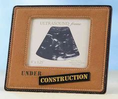 "Baby Under Construction Ultrasound Picture Frame  Display your ultrasound picture in a unique way with this ""Under Construction"" baby frame. The picture opening is 4"" x 3.25"". The entire frame measures 6.5"" x 5.5"" and is made of embroidered pleather"
