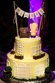 """This sweet cake is topped with Ellie and Carl's chairs from their house and a banner saying """"Mr. and Mrs."""""""