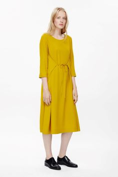 This dress is made from loose, fluid fabric with a tie fastening that can be worn on the front or back. Flaring towards the hem for an A-line shape, it has 3/4 sleeves, inside pockets and a wide round neckline.