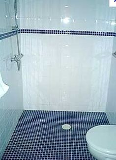 Fully tiled wet room with wheel in shower fold away wall hung