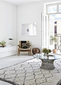 A cool white, minimal apartment, featuring the classic Nordic style of white painted floorboards...