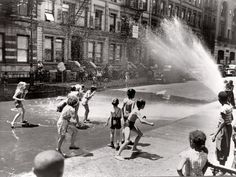 "New York, June 1943. ""Children escape the heat of the East Side by using fire hydrant as a shower bath."""