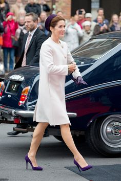 Crown Princess Mary matched her cream-coloured coat with purple gloves and purple shoes.