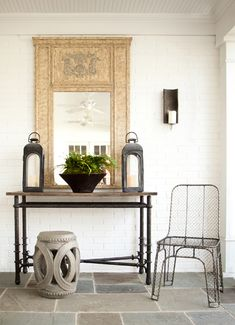 White beadboard covered patio, white exposed brick wall, French mirror, iron console table, slate tiles floor, Wisteria Interlocking Rings Stool and metal chair.