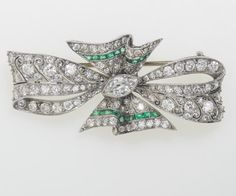 Platinum, Diamond and Emerald Pin - In the shape of a bow, circa 1920. Length 1 5/8 inches