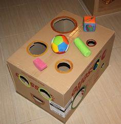 dit is ook een doos er hangen al dingetjes bovenop maar je kan ook dingen in de doos stoppen ze zien niet wat ze er uit halen tot het uit de doos is het is een uitdaging omdat de kinderen het uit de gaten moeten halen