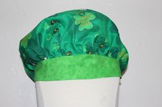 What a fun hat to wear to work for St. Patrick's Day. It is a bright green cap with four leaf clovers and Snoopy. It also says Happy St. Patrick's Day on it. It has a green brim on the front of the cap. The back of the cap is gathered with elastic. This cap is full enough to hold a long full ponytail. My daughter wears my scrub caps and she has very long thick hair and it all fits up inside very nicely. If you would like scrub caps made in any other fabric or for any holiday please send me a…
