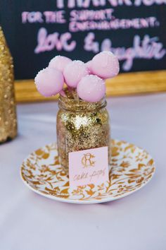 pink cake pops in a DIY glittery gold mason jar. Really makes them Dazzle! #cakepops #razzledazzle #pinkandgold http://www.weddingchicks.com/2013/12/06/gold-glam-wedding/