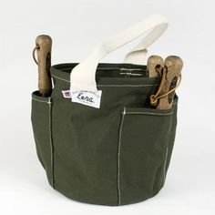 Eena Garden Tote. Each is locally crafted of 20 oz. canvas, a moisture resistant vinyl bottom, four outside tool pockets, and a 7 inch handle.