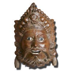 Máscara de madera con ojos de cristal y dientes de hueso