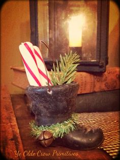 Wax Santa boot with greens and peppermint sticks by : Ye Olde Crow Primitives