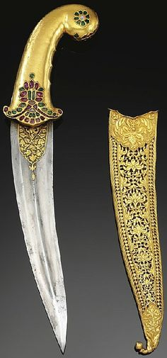 Indian (mughal) dagger, 17th century, curved double edged blade with cental ridge and damascened floral decoration around the forte, the hilt of yellow gold and curved round pommel set with rubies and emeralds with rosette and floral motifs, scabbard decorated with open work gold of all over vegetal and lotus blossom design terminating in a bud finial, 36cm.