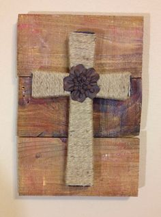 """Medium wooden pallet plaque. The reclaimed pallet boards are stained with a walnut danish oil and then distressed with white, yellow and red paint. It is then topped with a cross wrapped in burlap yard that features a rustic iron flower accent in the center.   Dimensions are approximately 11"""" x 16"""". Each cross is handmade with love and truly one of a kind."""