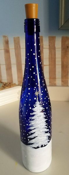 A family of snowmen are enjoying the snowfall as they gather around the Christmas tree. Hand painted on a cobalt blue wine bottle and is absolutely beautiful light up! I would be happy to customize the family to your specification..even down to the dog and or cat! The cobalt