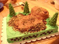 """My first theme cake - A guy I work with wanted a """"mudding"""" cake for his daughter.  This is what I came up with (he was supplying the truck).  I make a chocolate cake with buttercream and for the mud I made a fudge buttercream.  The hill is made from the original cake I made and it fell apart.  The dirt is oreos and graham crackers.  The trees are ice cream cones and royal iciing.  I had a lot of fun with this one."""