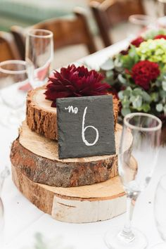 A slate table number sits on rustic tree slices topped by a dahlia.