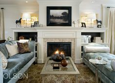 SPACE & LIGHT RENO. Marble tile frames the new gas fireplace on all four sides for a fresh update. Working a TV into the room in an unobtrusive way, we installed it behind a framed painting placed over the mantel. The original stained glass windows hold a prominent place above the detailed cabinetry. #candiceolson
