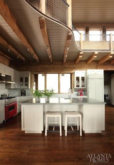 """""""The concept was to create a lowered ceiling above kitchen to keep it from being too volumetric,"""" Harrison says of the decision to add the landing above the cooking space. """"It makes the kitchen more intimate, but allows for a more sculptural space that continues up the staircase into the second-story area."""""""