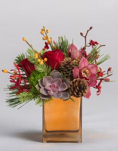 Winterberry A design favorite, this unique cluster of orchids, roses, wintery greens and seasonal textures is arranged in a shimmery copper cube #robertsonsflowers