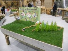 sod raised play table for kids.. farm, fence, horses, toys...THIS was at Seattle's Northwest Garden Show... the annual show is HUGE, kids are free, and they ALWAYS have a play garden set up for kids... that year's play garden theme was Charlotte's Web (there was a petting zoo behind with FULL SIZED versions of Charlottes spun words)