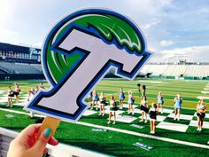 This student shows off their Tulane Green Wave pride and the cheerleaders at Yulman Stadium