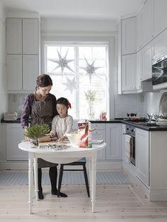 STÄMNINGSFULL JUL I VACKERT SEKELSKIFTESHUS: När Pernilla och Cornelia ska baka kommer det lilla antika slagbordet fram. Köket är från Ikea och Pernilla har målat luckorna med ljusgrå linoljefärg. Stjärnor i fönstret, Länna möbler | Julreportage i Lantliv - Made in Persbo