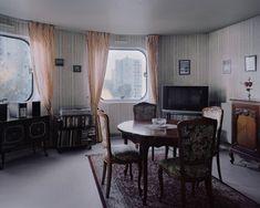 A nanterre-i Picasso-város egyik elegánsan puritán lakása, ahol jól megfér egymás mellett a praktikusan szép biedermeier bútor és a plazmatévé. A fotó ugyan 2014-es, de az időtlenséget sugárzó szobabelső, ami a fotóriporter Kronentalt is teljesen lenyűgözte, akár egy futurisztikusan retró sci-fiben is megállná a helyét. Szinte már várjuk, hogy bejöjjön Jules Verne vagy Conan Doyle, és lelkesen mesélni kezdjen a következő kalandregénye dinoszauruszokat kergető, Holdra utazó, víz alatti…