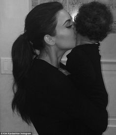 'Night!' Kim Kardashian posts adorable snap of herself kissing daughter North before bedtime on Wednesday evening