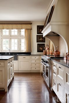 Olive-green countertops, a honed granite sink and a custom plaster hood are showstoppers in the kitchen.