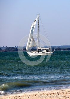 A single white  yacht with white sails sailing on a calm sea in West Wittering in Sussex.